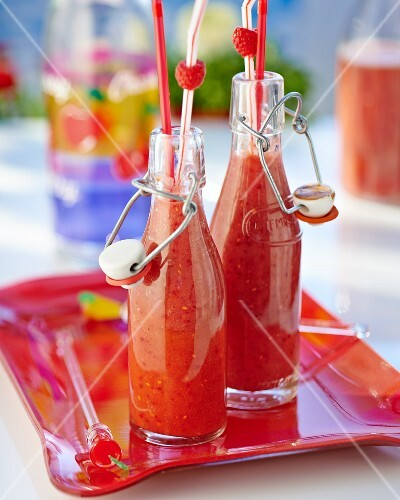 Homemade peach and raspberry smoothies in glass bottles