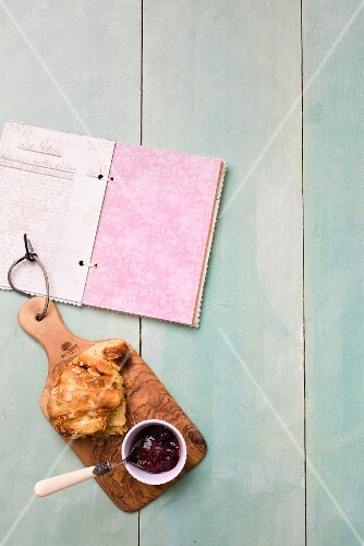 Almond pastries with jam on a wooden board next to a book