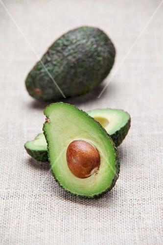 Avocados, whole and halved, on a fabric surface