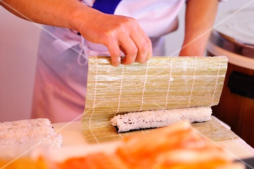 Sushi being made: rice being rolled in a bamboo mat