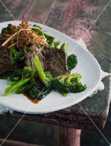 Broccoli with ginger and beef on a pink wooden table