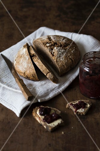 Sourdough bread with homemade jam on a rustic wooden surface