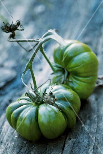 Two large, green beefsteak tomatoes on a wooden surface