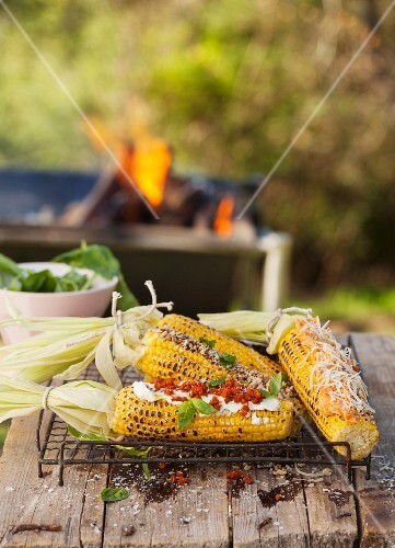 Grilled corn cobs with various accompaniments