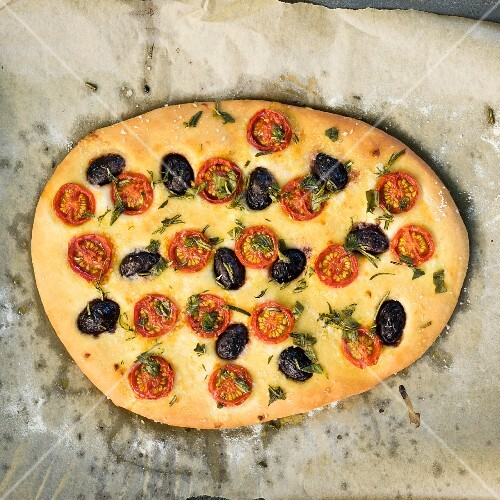 Vegan focaccia with cherry tomatoes and black olives