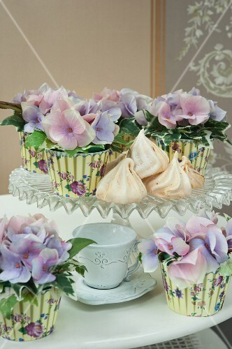 Purple hydrangea flowers in pots covered with printed muffin cases on a cake stand