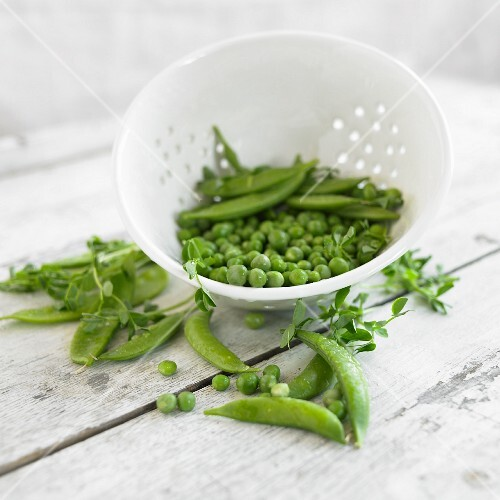 Fresh pea pods and peas in a colander