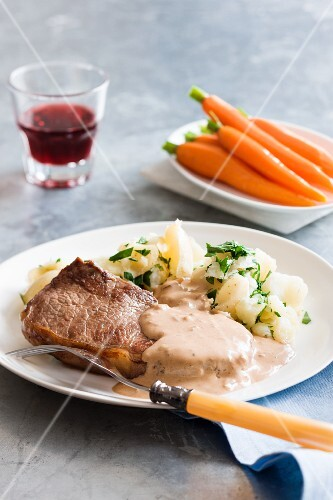 Steak Diana with mashed potatoes and carrots