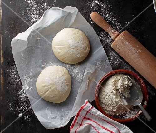 Two balls of pizza dough on a piece of paper with flour and a rolling pin