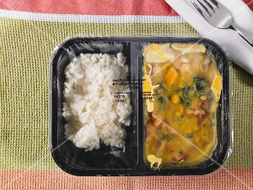 Pre-cooked and frozen chicken curry as a ready meal in a segregated plastic package