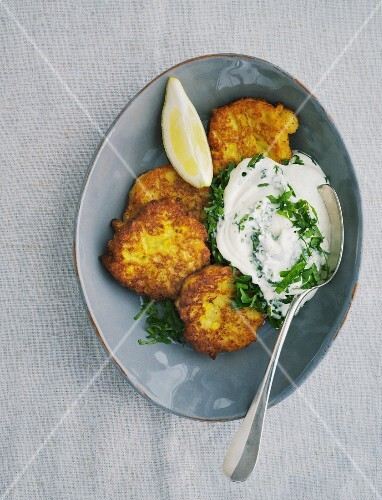 Corn cakes with herb cream and lemon wedges