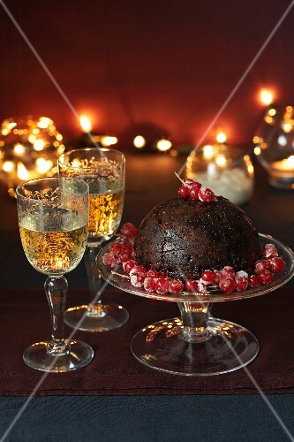 Christmas pudding with redcurrants and two glasses of white wine