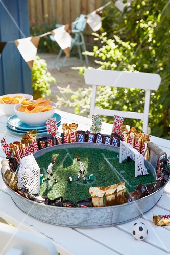 Stylised football pitch on metal tray with artificial grass and toy figurines as table decoration for football-themed party