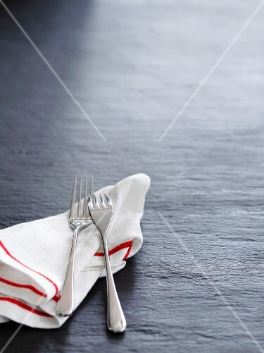 A tea towel and two forks on a slate surface
