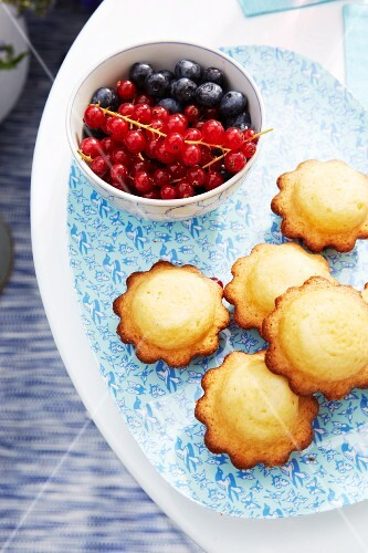 Summer berry fruits and muffins on a delicately patterned serving plate