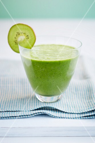A glass of kiwi smoothie garnished with a slice of kiwi