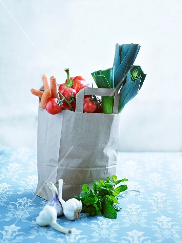 An arrangement of vegetables with a paper bag