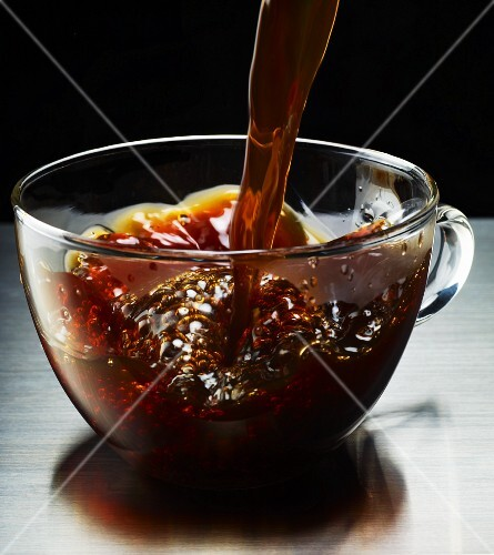 Black coffee being poured into a glass mug
