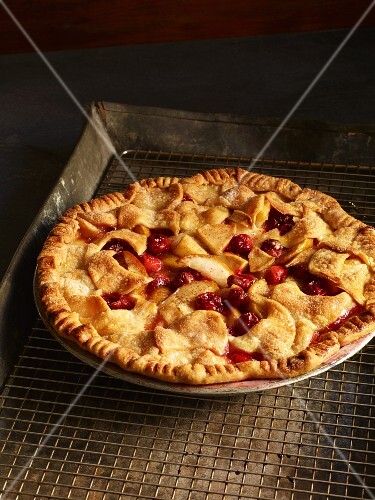 A whole berry pie on a cooling rack