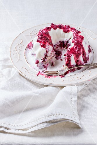 Ice cream cake with berry sauce on a vintage plate