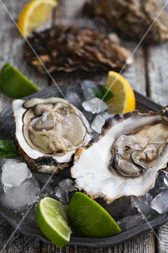 Fresh, raw oysters with slices of lemon and lime