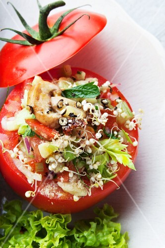 A tomato filled with quinoa sprouts and vegetables