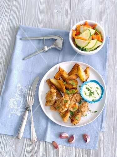 Chicken nuggets with garlic sauce, potato wedges and a courgette and pepper salad