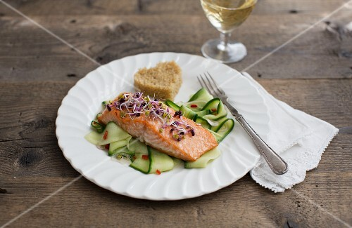 Salmon fillet with bean sprouts on a cucumber salad with a heart-shaped piece of bread