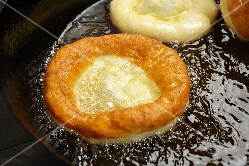 Bauernkrapfen (Austrian yeast dough pastries) being fried in a pan of oil