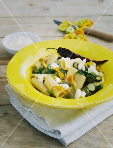 Rigatoni with mini courgettes in a yellow plate