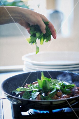 Hands adding wild garlic to a pan