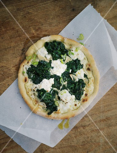Spinach pizza on a piece of paper on a wooden table