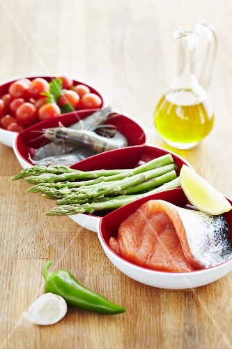 A bowl of ingredients: tomatoes, prawns, asparagus and salmon fillet