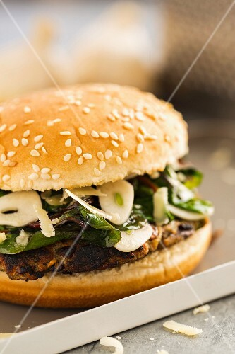 A vegetarian burger with a bean patty, sautéed garlic-spinach and grated Parmesan