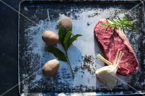 Beef steak, garlic, spices, herbs and potatoes on a baking tray
