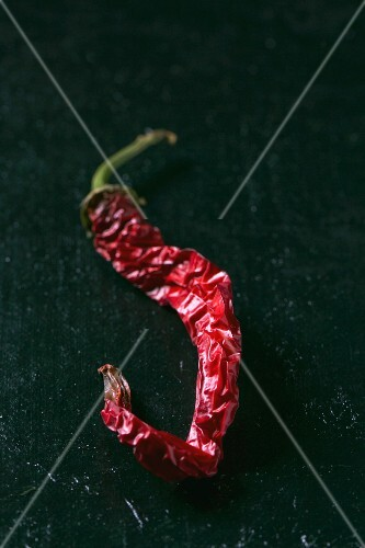 A dried red chilli pepper on a dark surface