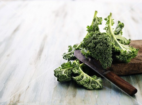 Fresh green kale leaves on a chopping board with a knife