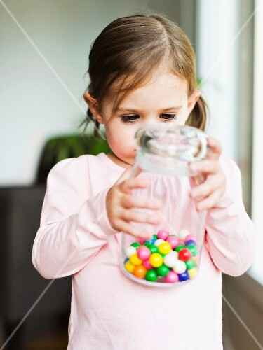 A little girl holding a jar of sweets