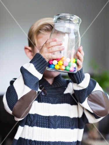 A little boy holding a jar of sweets