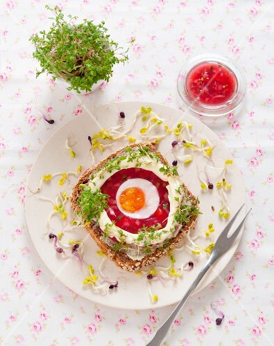 A slice of wholemeal bread topped with beetroot aspic, egg, mayonnaise, cress and radish sprouts