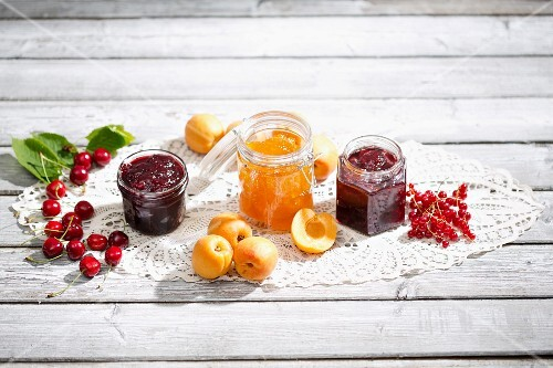 Cherry jam and cherries, apricot jam and apricots, redcurrant jam and redcurrants on a doily