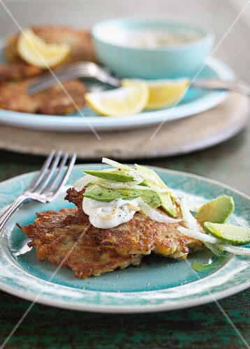 Corn fritters with sour cream and an avocado and onion salad