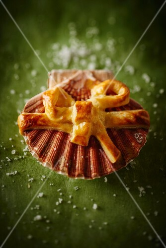 A puff pastry bow on top of a scallop