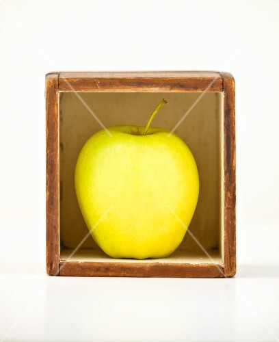 A Golden Delicious apple in a small box