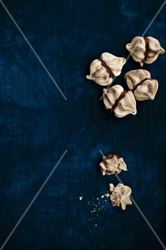 Mini meringues filled with coffee cream, one partly eaten (seen from above)