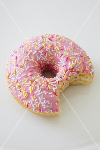 A pink iced doughnut with sugar sprinkles and a bite taken out