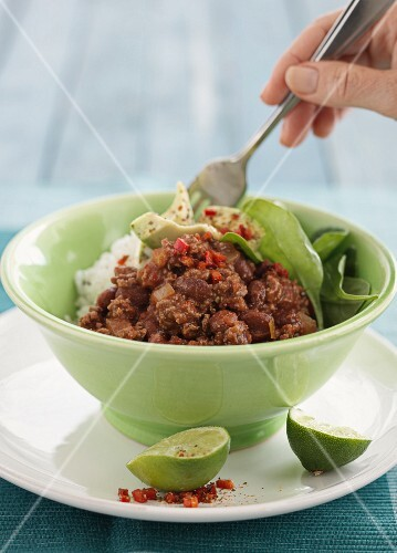 Chilli con carne with rice and limes