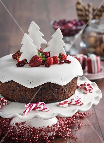 A Christmas cake with berries and fondant trees
