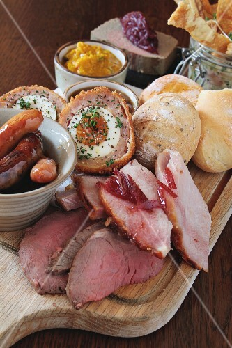 A ploughman's lunch featuring ham, sausages, Scotch eggs, chutney and bread rolls (England)