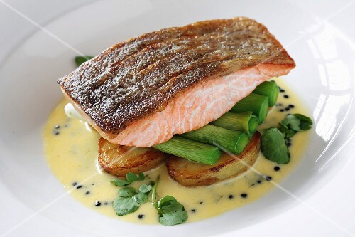 Salmon fillet on a bed of leek and potatoes in Hollandaise sauce